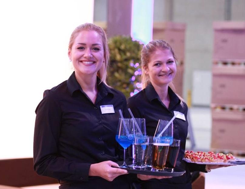 Zwei Servicekräfte mit Getränken und Fingerfood